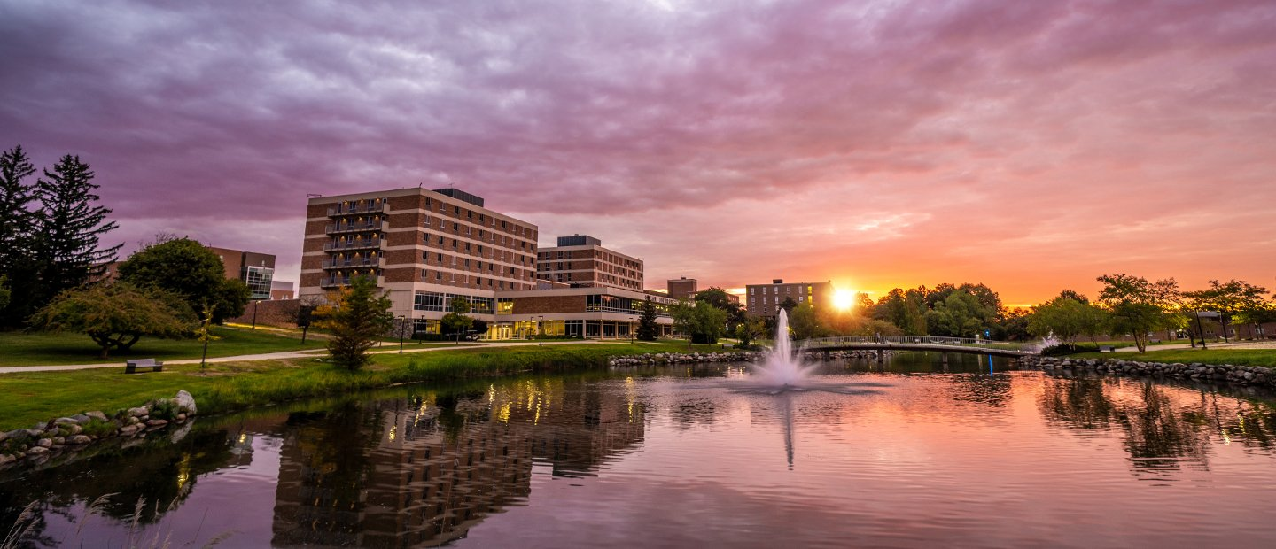 Bear Lake and buildings on Oakland University's campus with a purple and orange sky.