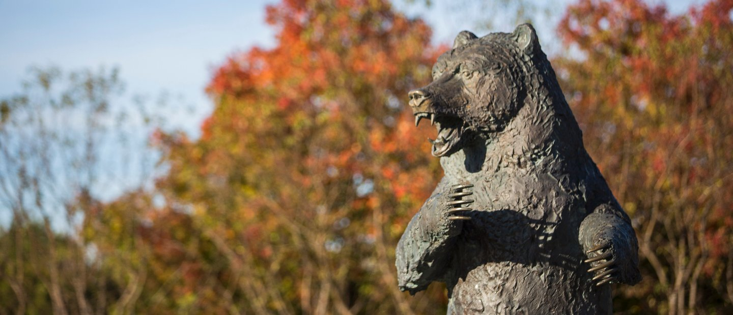 The Grizz bear statue in front of trees with red and green leaves.