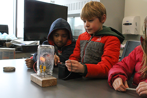 two kids working with a device that creates electricity in a jar