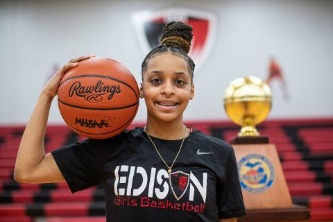 Damiya Hagemann holding a basketball on her shoulder, standing in front of a trophy, smiling at the camera