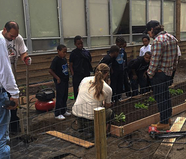 Group of Dove Academy of Detroit students learn to build garden beds with staff members