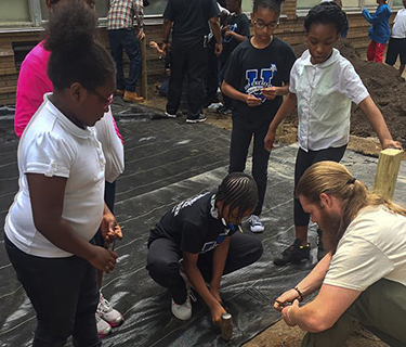Group of Dove Academy of Detroit students learn to build garden beds with a staff member