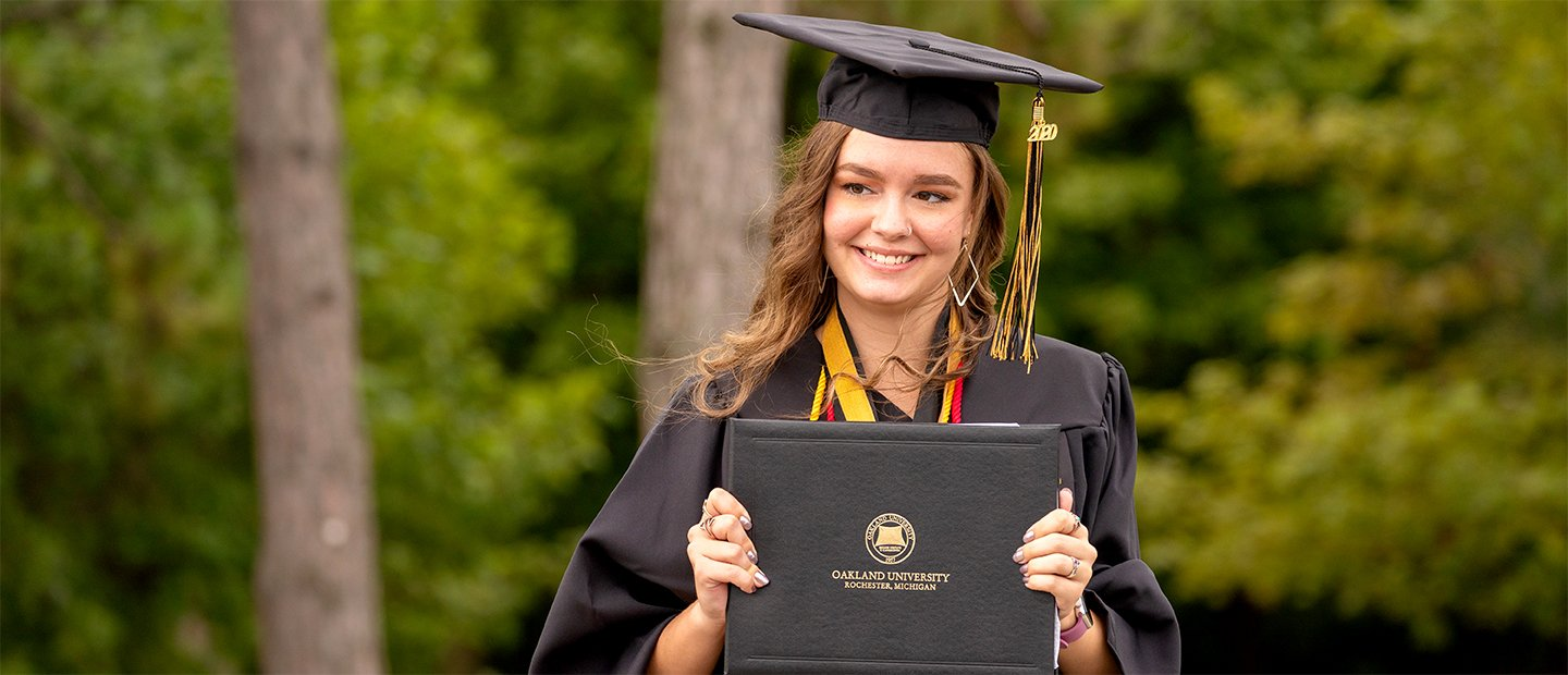 A female Oakland University graduate, wearing a cap and gown, holding up a diploma.
