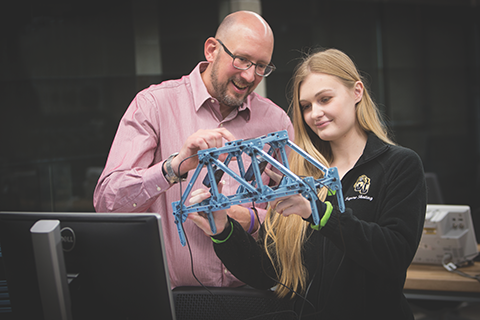 male professor and female student holding a blue engineering model