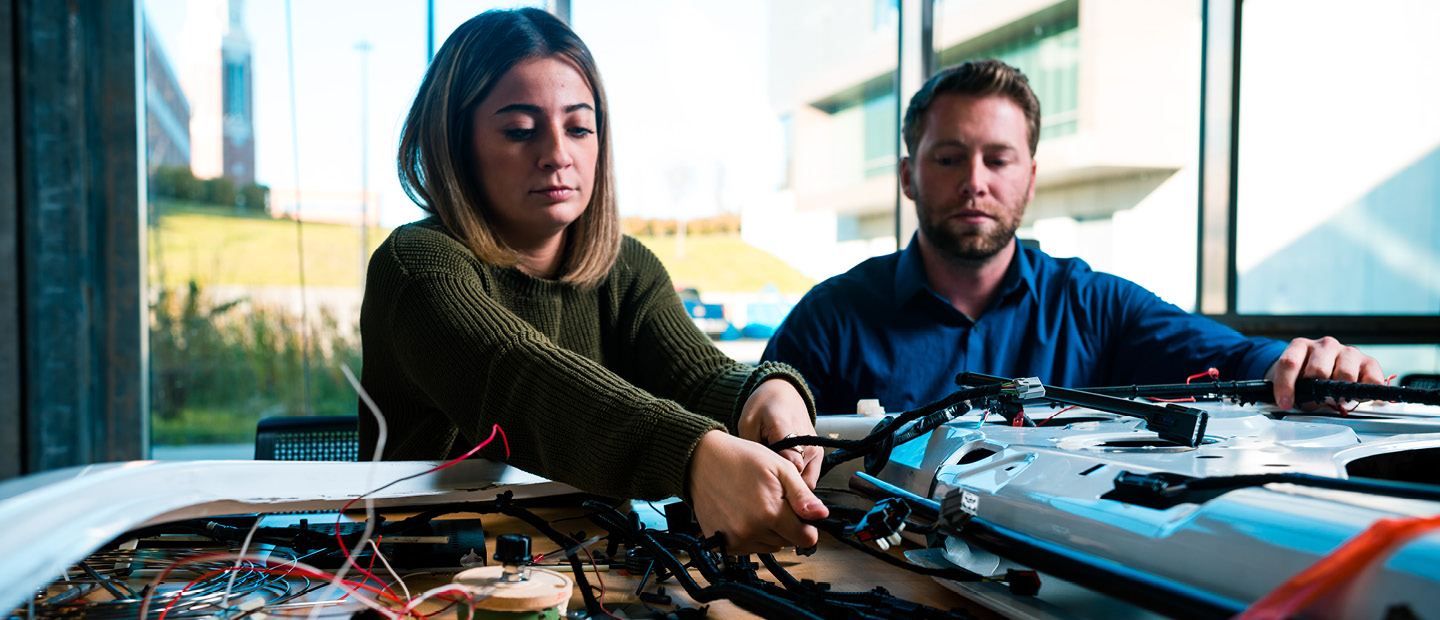 man and woman working on an electrical circuit board with wires