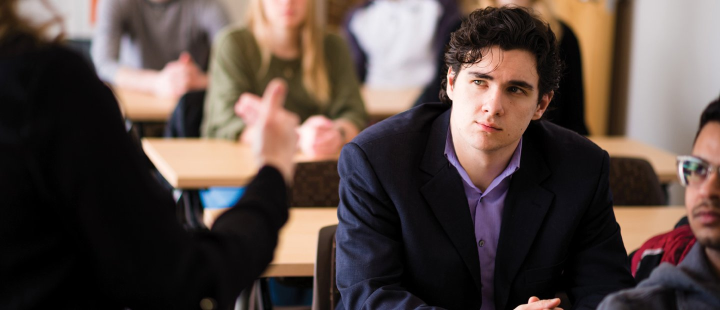 young man in a classroom full of students, watching someone at the front of the room