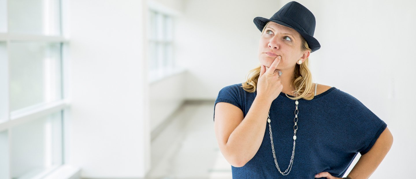 woman in a blue shirt and hat with her hand on her chin and an inquisitive look on her face