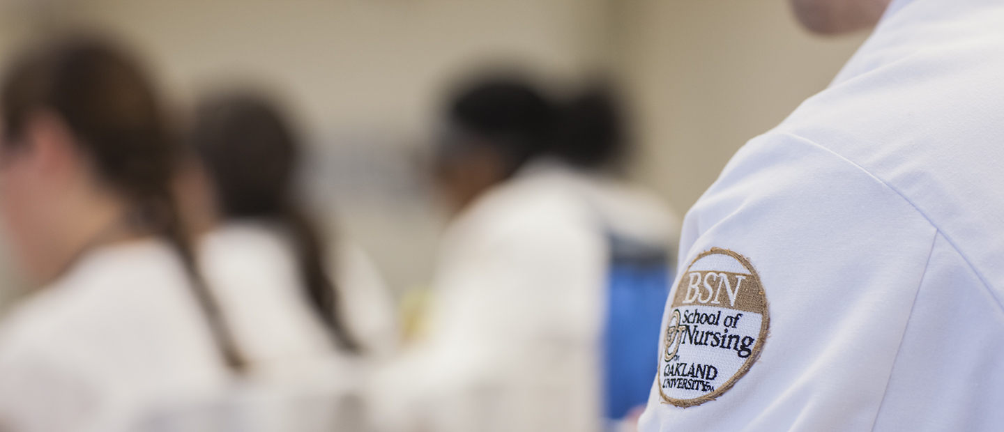 A person in a white lab coat with an Oakland University B S N School of Nursing patch on the arm.