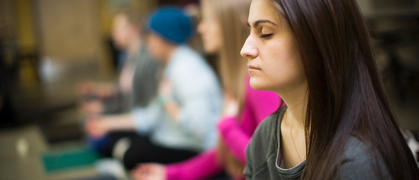 Woman with her eyes closed, meditating in a class.