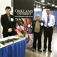 students standing in front of their table at a conference