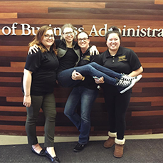 group shot of four women in front of the school of business administration sign