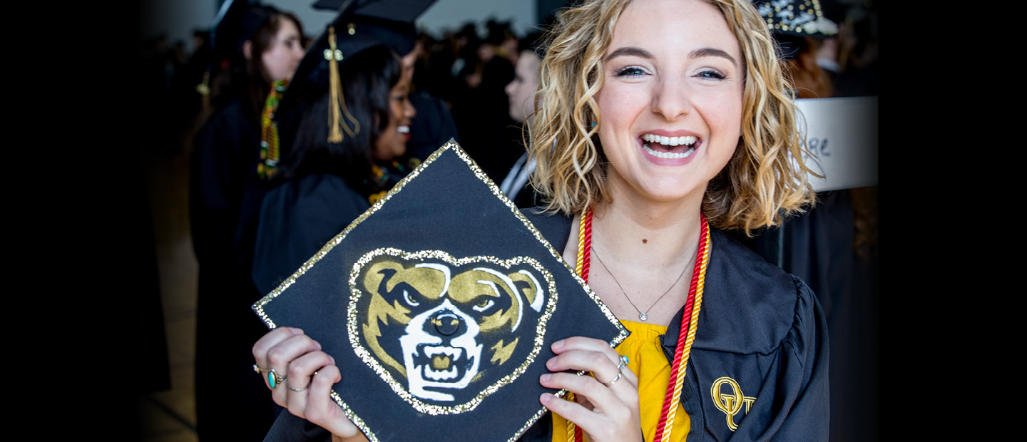 student with blonde hair holding commencement cap with a photo of the grizz on it in her commencement regalia