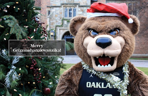 Happy Grizzmahanakwanzika greeting with Grizz in a Santa hat in front of Meadow Brook Hall