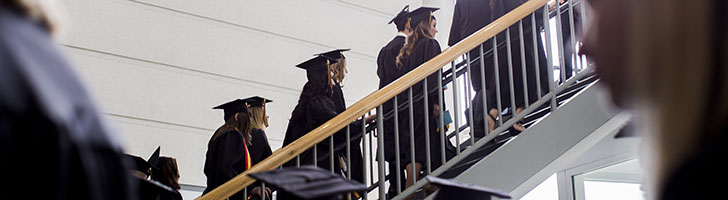 Graduating students in cap and gown walk up stairs