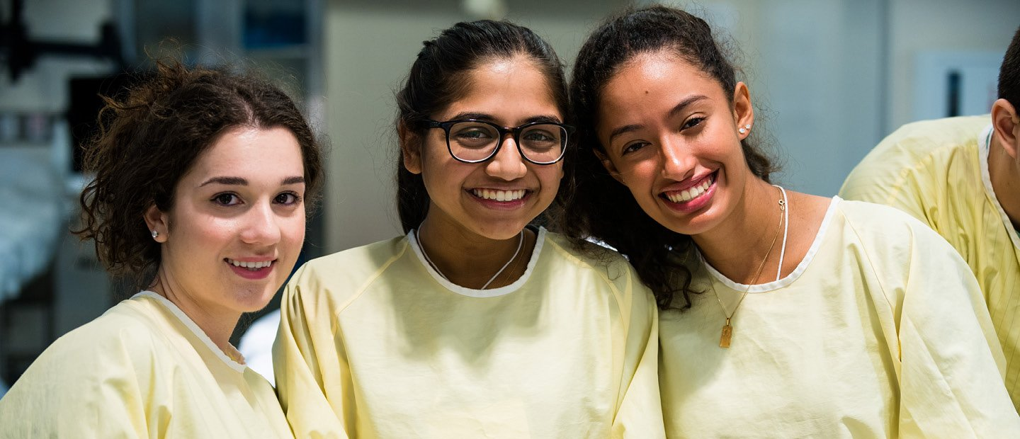 three female students in yellow lab coats