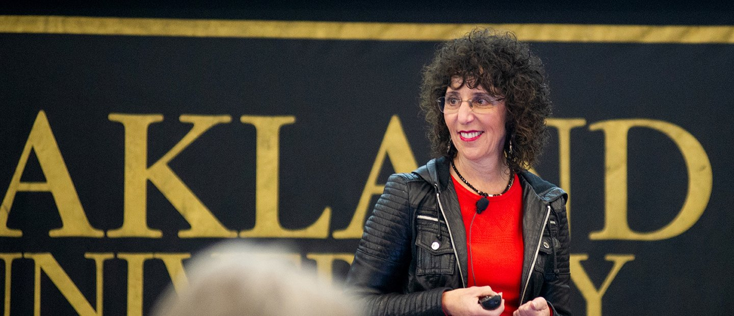 President Ora Hirsch Pescovitz standing in front of a black and gold Oakland University banner.