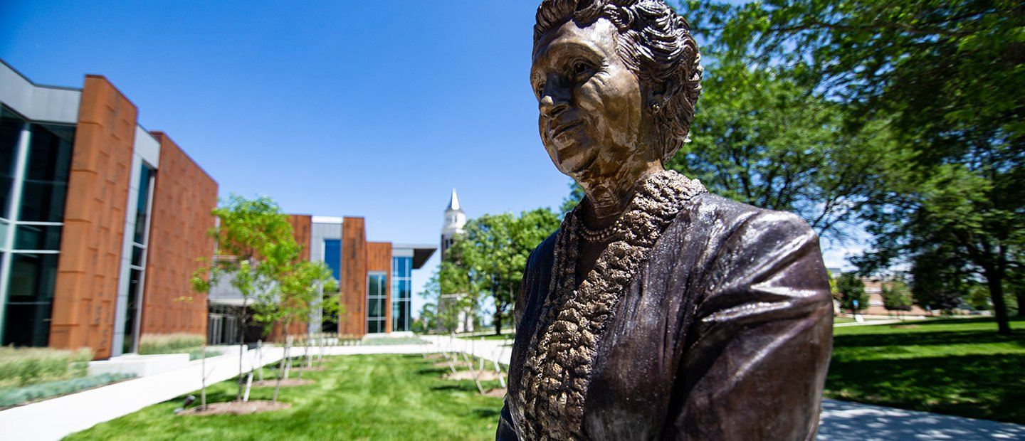 A bronze statue of a woman outside of a building on Oakland University's campus.