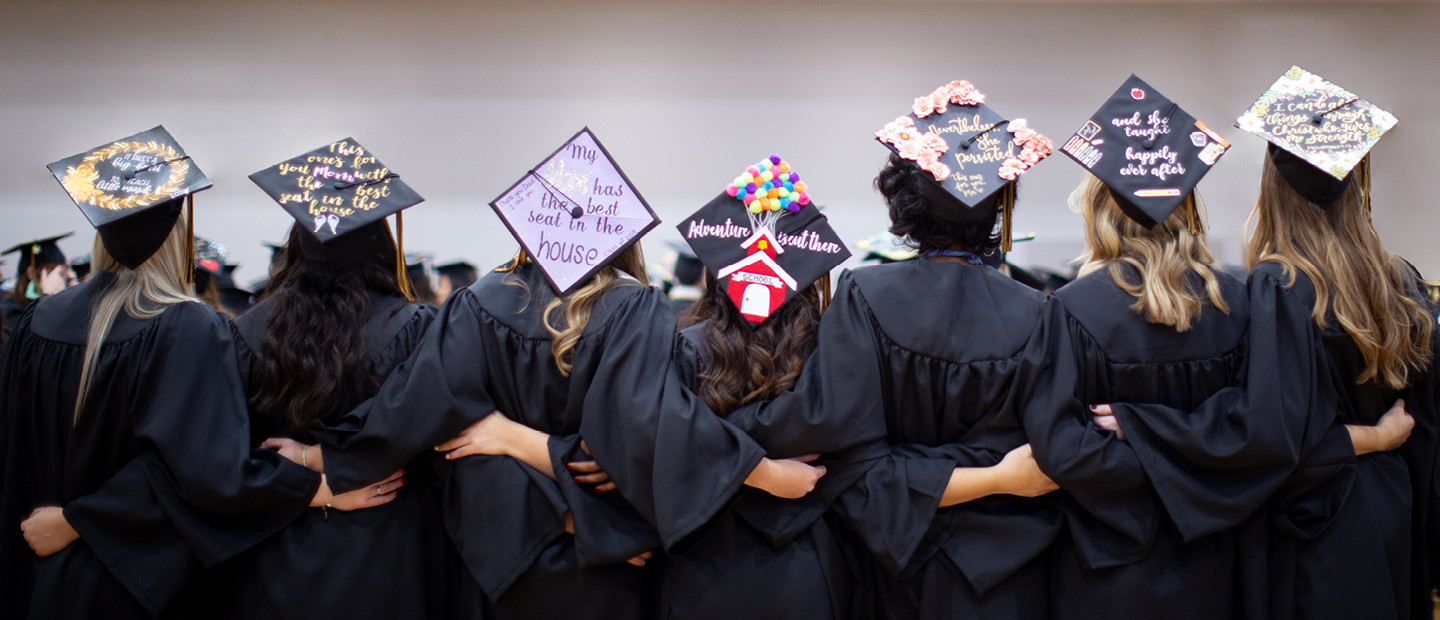 seven girls standing in their regalia with the top of their commencement caps decorated