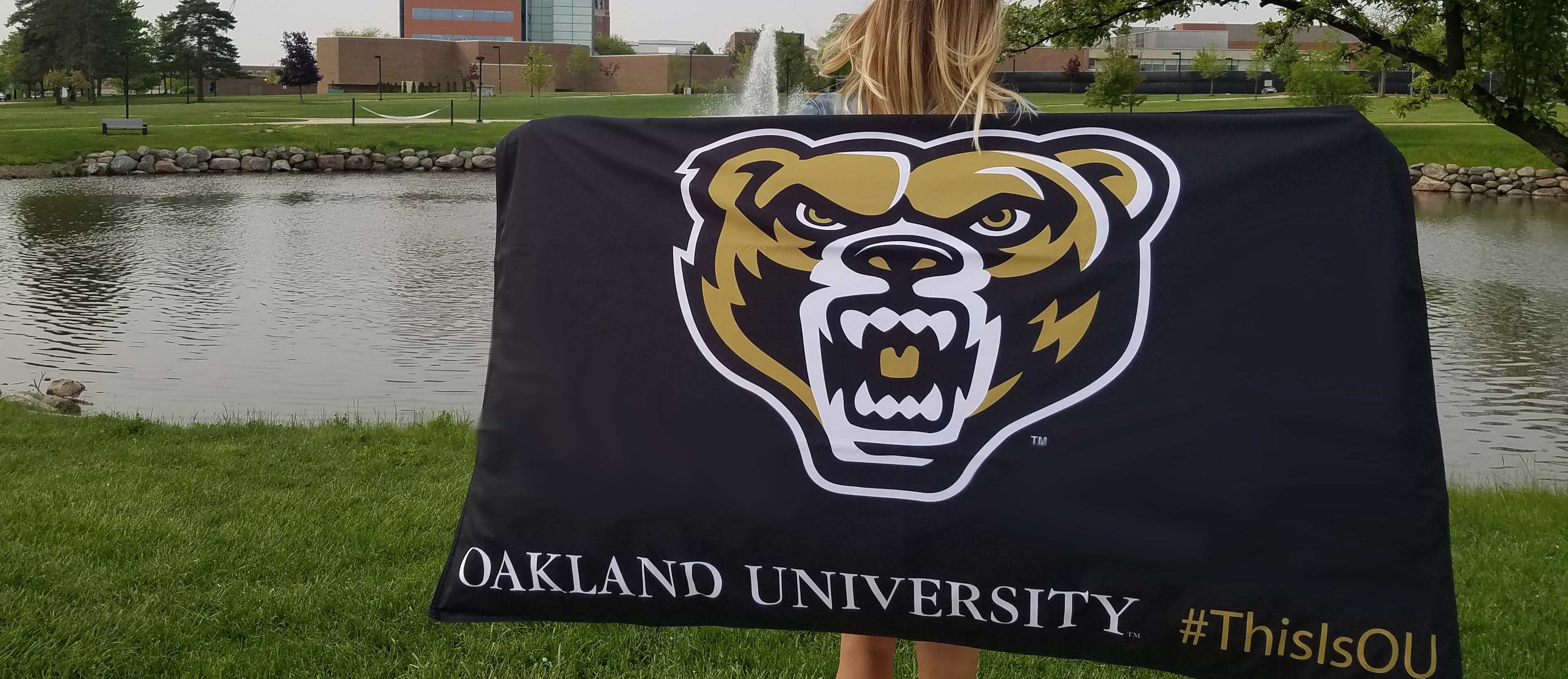 Woman holding a 3-foot by 5-foot flag in front of Bear Lake. Flag has the bear head and Oakland University #ThisIsOU printed on it.